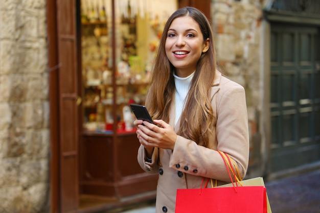 Mooie mode vrouw met boodschappentassen online winkelen met slimme telefoon in de straat op kersttijd camera kijken.