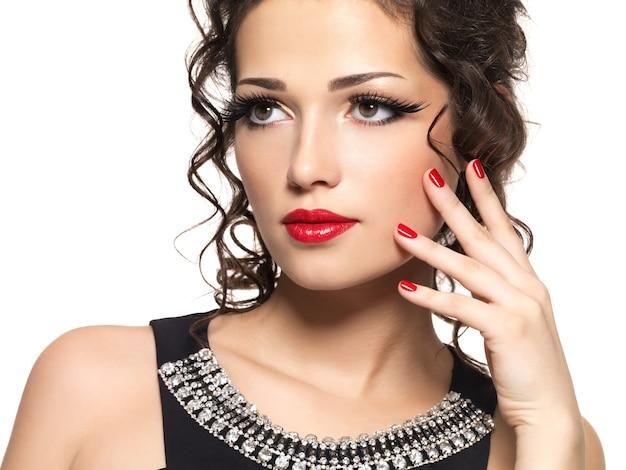 Mooie mode vrouw met rode manicure en lippen -