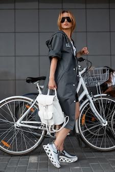 Mooie model jonge vrouw in zonnebril in een lange jas in sneakers met een rugzak loopt door de stad in de buurt van een modern gebouw. aantrekkelijk meisje staat in de buurt van een vintage fietsen. gezonde levensstijl.