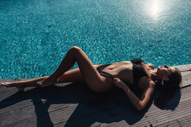 Mooie model vrouw in een zwarte bikini ontspant in de buurt van het zwembad. strandmode zomerkleding. kopieer ruimte