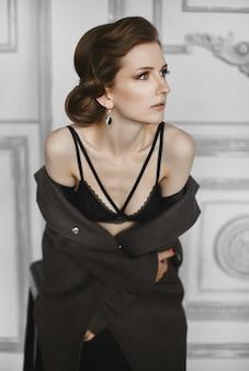 Mooie model vrouw met trendy kapsel en avond make-up in zwarte lingerie en losgeknoopte jas poseren binnenshuis. mode portret van prachtig modieus model meisje
