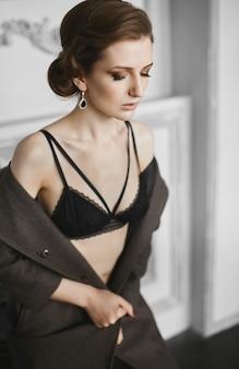 Mooie model vrouw met trendy kapsel en avondmake-up in zwarte lingerie en losgeknoopte jas poseren binnenshuis