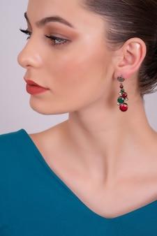 Mooie modelbrunette met lang haar en juwelen die oorbel dragen