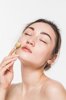 Mooie modelvrouw die met gezonde verse schone huid geniet van een massage met een jade gezichtsrol om de bloedsomloop te verbeteren, de spieren te ontspannen en de huid te versterken, geïsoleerd op grijze muur met exemplaarruimte