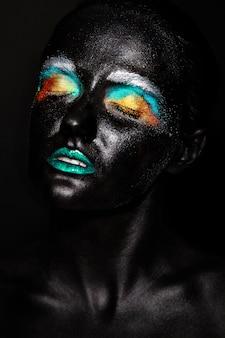Mooie modelvrouw met creatief plastic ongebruikelijk zwart masker heldere kleurrijke make-up met zwart gezicht