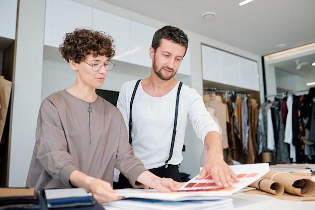 Mooie modeontwerper en haar collega kijken door kleurstaalset terwijl ze erover praten