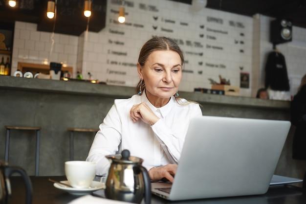 Mooie moderne europese vrouwelijke freelancer van middelbare leeftijd die ver op de draagbare computer werkt, in cafetaria zit en cappuccino heeft. oudere vrouw schrijver met behulp van laptop voor extern werk in café