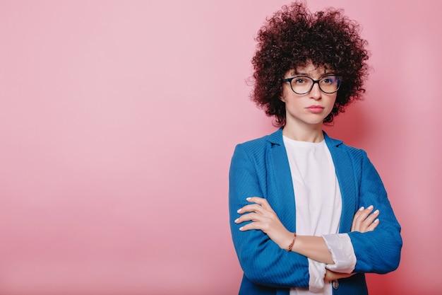 Mooie moderne vrouw gekleed jasje en bril vormt op roze met ernstige emoties en gevouwen handen