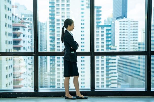 Mooie moderne zakenvrouw permanent in de buurt van venster in moderne kantoren.