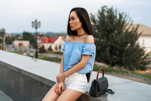 Mooie modieuze aziatische vrouw in een blauwe blouse en witte korte broek met een tas zit op een van de stad.