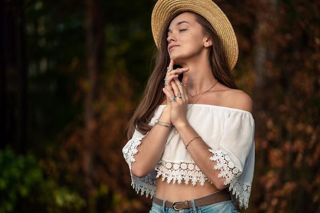 Mooie modieuze boho chique vrouw in strohoed en in een witte korte blouse met zilver turquoise sieraden