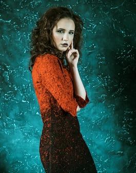 Mooie modieuze brunette vrouw in rode jurk