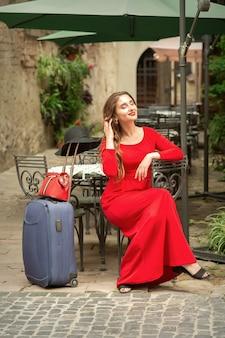 Mooie modieuze jonge blanke vrouw reiziger lange rode jurk met koffer dragen in het restaurant buiten