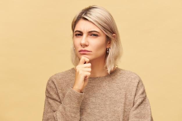 Mooie modieuze jonge verdachte europese vrouw in kasjmier pullover hand op haar kin te houden en te staren met achterdocht en wantrouwen, ogen verknoeid. menselijke gezichtsuitdrukkingen