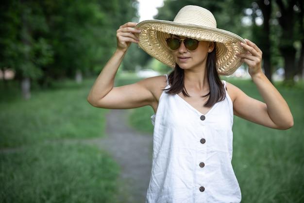 Mooie modieuze jonge vrouw die strohoed en zonnebril in openlucht draagt.