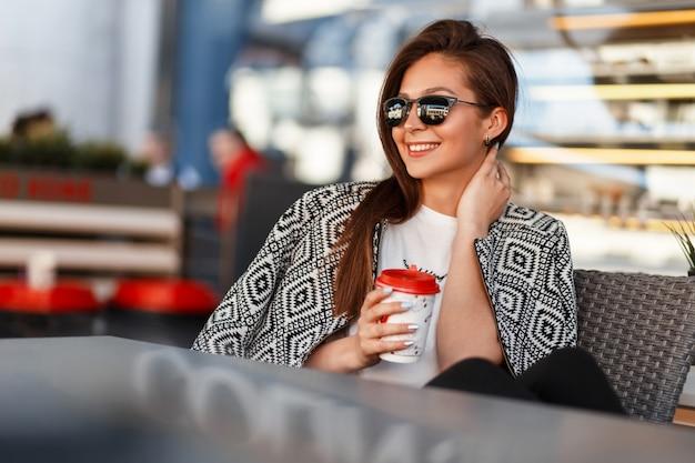 Mooie modieuze jonge vrouw met koffie in zonnebril met stijlvolle modieuze kleding rusten in een restaurant op straat