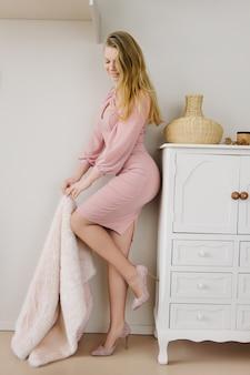 Mooie modieuze jonge vrouw met lang blond krullend haar in een roze poederachtige jurk en suède schoenen blijven in een gezellig interieur.