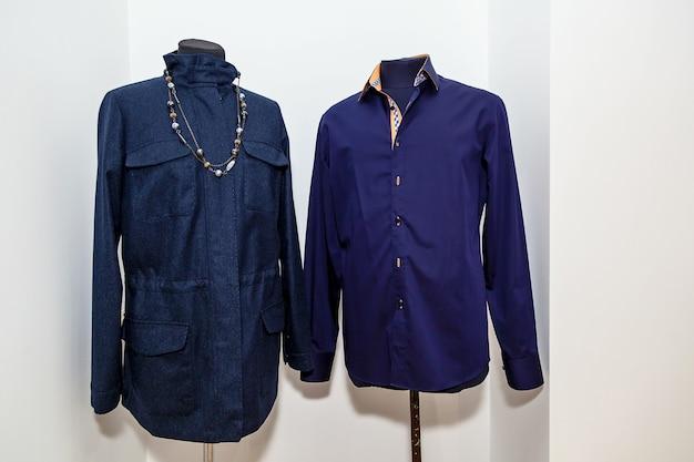 Mooie, modieuze jurk en handgemaakt overhemd, op een mannequin, een atelier voor kleermakerswerk