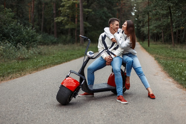 Mooie modieuze paar in stijlvolle denim kleding en rode schoenen met een elektrische scooter in een park op de weg