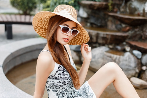 Mooie modieuze stijlvolle meisje in zonnebril en hoed rusten op een zomerdag.