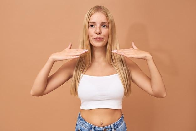 Mooie modieuze tienermeisje met neuspiercing, sproeten en losse haren met handpalmen op haar hoofd om polijstmachine droog te krijgen op haar nagels