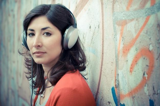 Mooie modieuze vrouw die aan muziek luistert