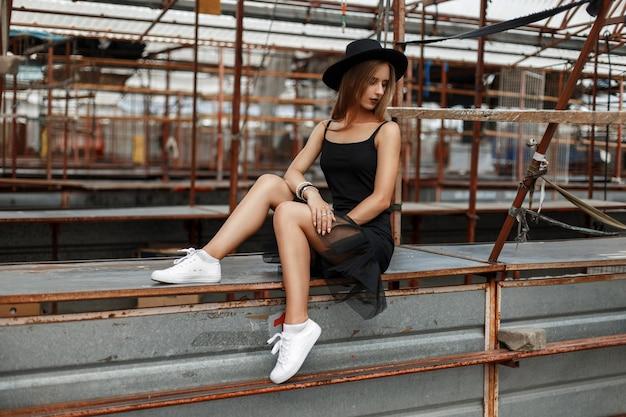 Mooie modieuze vrouw in een zwarte rok met witte sneakers en een stijlvolle hoed zit op de markt