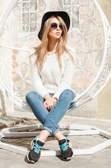 Mooie modieuze vrouw zittend in een witte hangende stoel