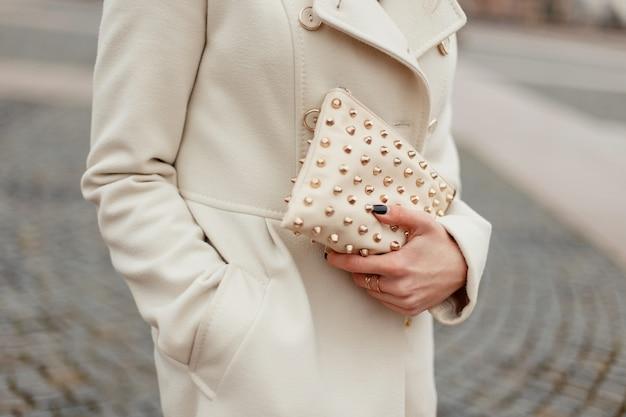 Mooie modieuze vrouwelijke tas. modelmeisje in een trendy jas met een modetas