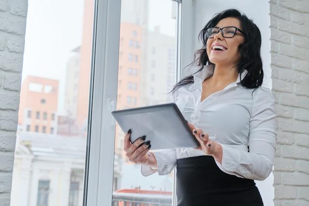 Mooie modieuze zakenvrouw met digitale tablet.