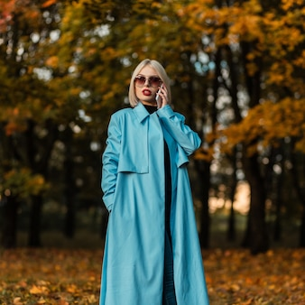 Mooie modieuze zakenvrouw met zonnebril in modieuze blauwe jas praten aan de telefoon in een herfstpark met helder kleurrijk herfstgebladerte