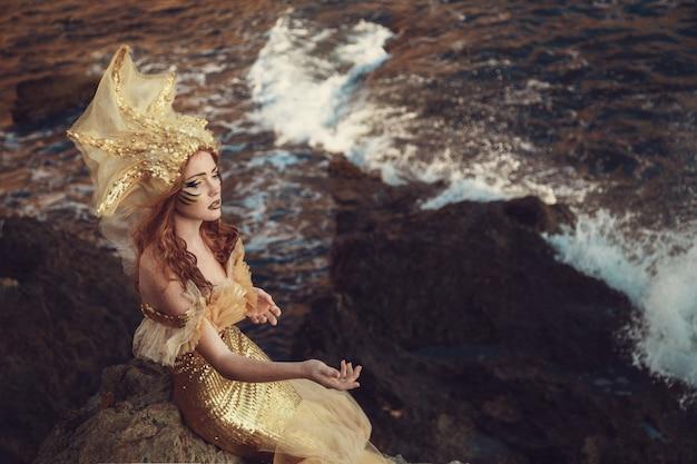 Mooie modieuze zeemeermin zittend op een rots aan zee