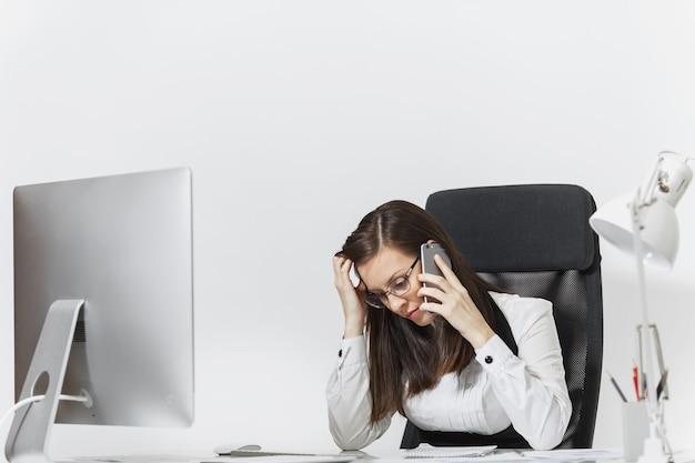 Mooie moe en stress zakenvrouw in pak zitten aan de balie, werken op moderne computer met documenten in licht kantoor, praten op mobiele telefoon, problemen oplossen