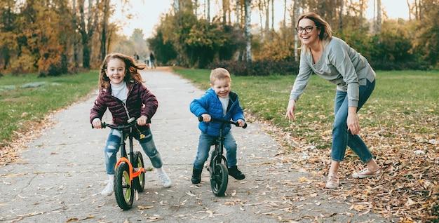 Mooie moeder die een wandeling in het park maakt met haar kinderen die hen leren fietsen