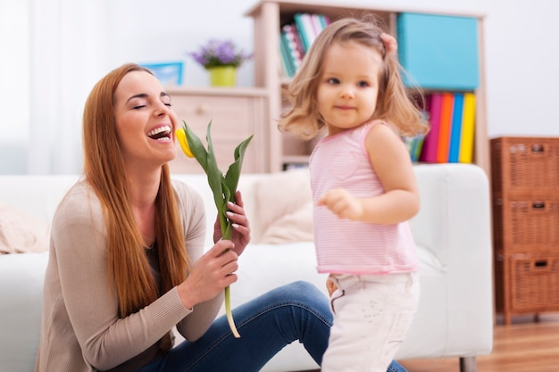 Mooie moeder die geniet van de bloem die ze van haar dochter ontving