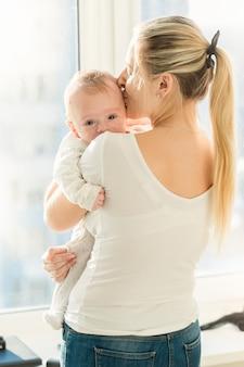 Mooie moeder die haar 3 maanden oude babyjongen omhelst bij het raam