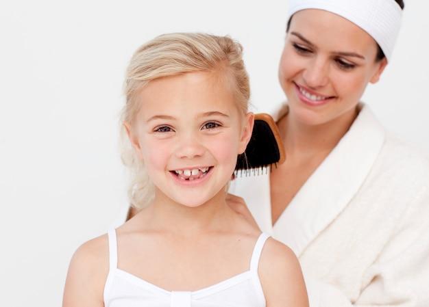 Mooie moeder die het haar van de dochter doet