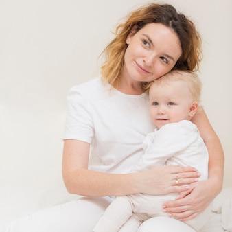 Mooie moeder die leuk babymeisje houdt