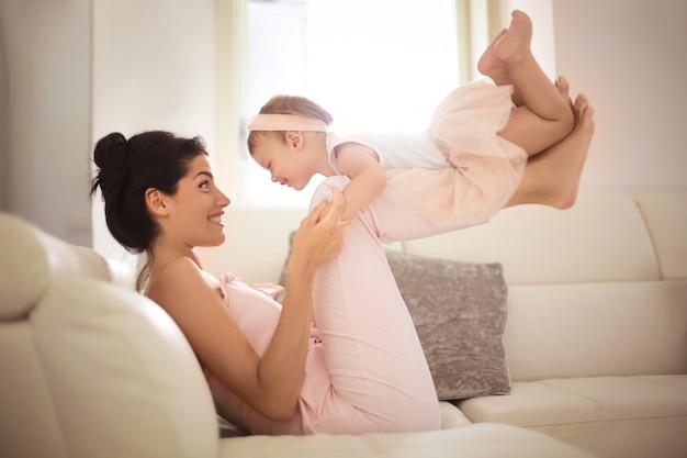 Mooie moeder die op de bank met haar dochter speelt