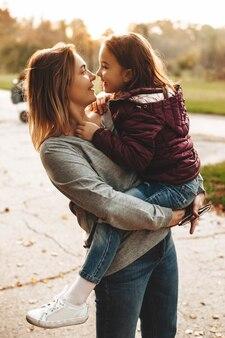 Mooie moeder die op haar wapens haar dochter houdt die haar tegen student in het park bekijkt.