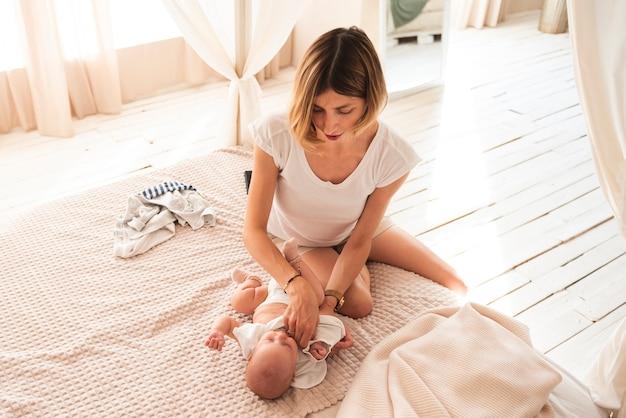 Mooie moeder die pasgeboren baby kleedt
