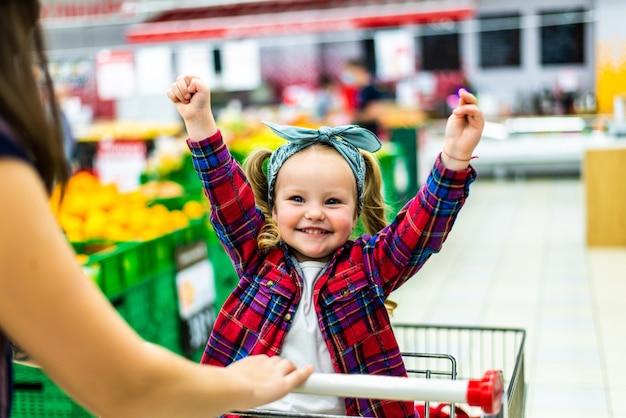 Mooie moeder draagt haar kleine meisje in de supermarktwagen