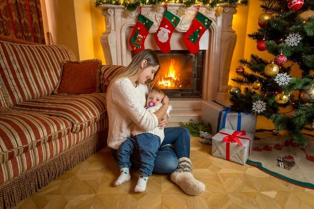 Mooie moeder en baby zittend op de vloer bij open haard versierd voor kerstmis