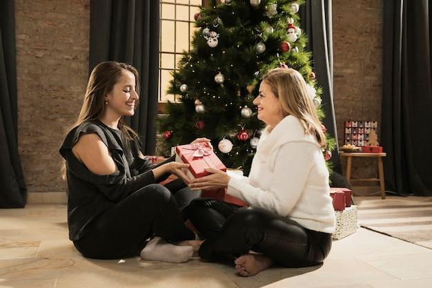 Mooie moeder en dochter die cadeaus uitwisselen