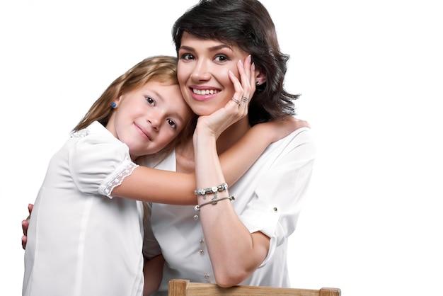 Mooie moeder en dochter, die haar knuffelen. ze zien er erg blij uit, glimlachen en dragen witte t-shirts.