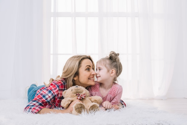 Mooie moeder en dochter die op bont liggen die grappig gezicht met teddybeer maken