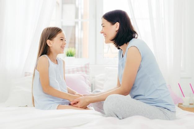 Mooie moeder en dochter genieten van saamhorigheid, houden de hand bij elkaar, hebben een prettig gesprek