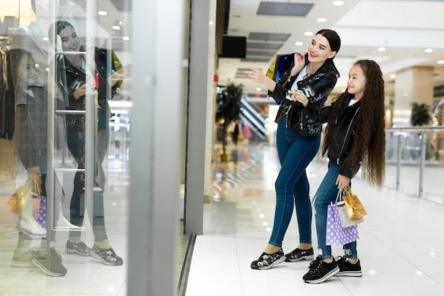 Mooie moeder en dochter glimlachen tijdens het winkelen in het winkelcentrum
