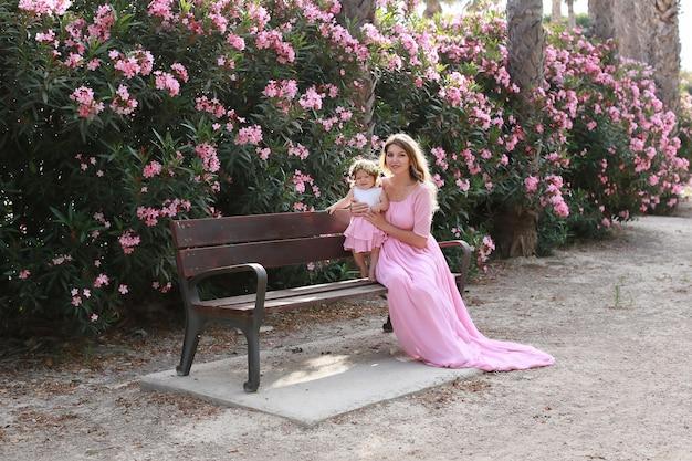 Mooie moeder en dochter in soortgelijke jurken op het park in de buurt van bloemen in zonnige zomerdag