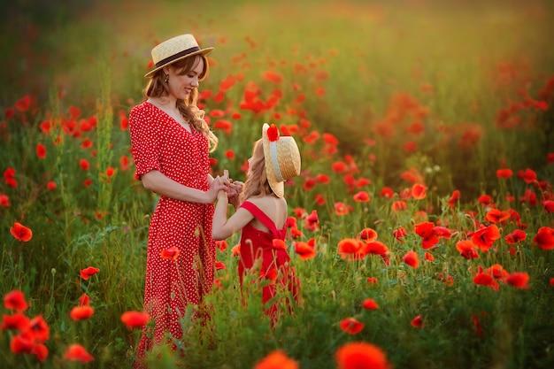 Mooie moeder en dochter in strooien hoeden en rode jurken omhelzen elkaar in het voorjaar op een descriptie ... in de bergen.